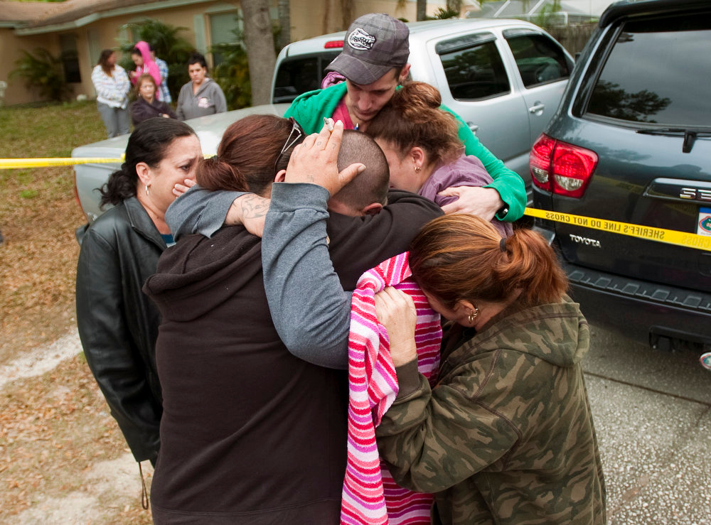 . Jeremy Bush, center with hand on head, is embraced by family and friends outside his home at 420 Faithway Drive in Seffner, Fla. Friday, March 1, 2013.  In a matter of seconds, the earth opened under Jeff Bush\'s bedroom and swallowed him up like something out of a horror movie. About the only thing left was the TV cable running down into the hole. Bush, 37, was presumed dead Friday, the victim of a sinkhole ó a hazard so common in Florida that state law requires home insurers to provide coverage against the danger. (AP Photo/The Tampa Tribune, Chris Urso)
