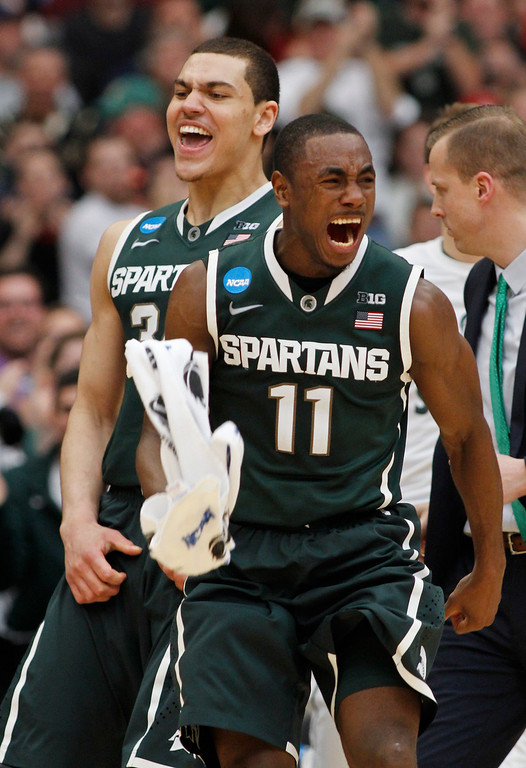 . Michigan State\'s Lourawls Nairn Jr. (11) and Gavin Schilling (34) react during the second half of a regional final against Louisville in the NCAA men\'s college basketball tournament Sunday, March 29, 2015, in Syracuse, N.Y. (AP Photo/Nick Lisi)