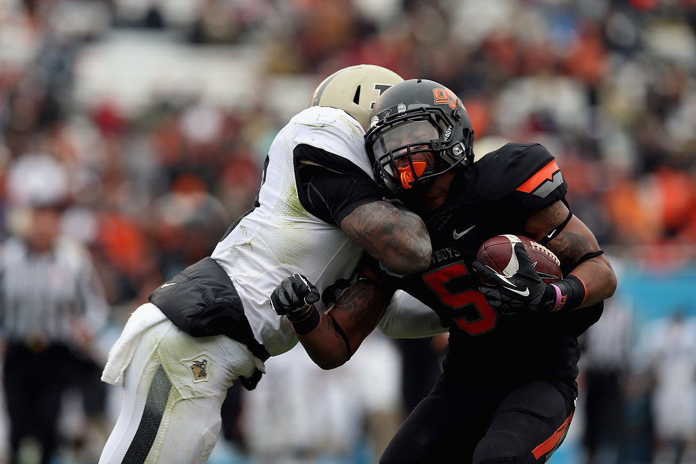 Description of . Josh Stewart #5 of the Oklahoma State Cowboys is tackled by Josh Johnson #28 of the Purdue Boilermakers during the Heart of Dallas Bowl at Cotton Bowl on January 1, 2013 in Dallas, Texas.  (Photo by Ronald Martinez/Getty Images)