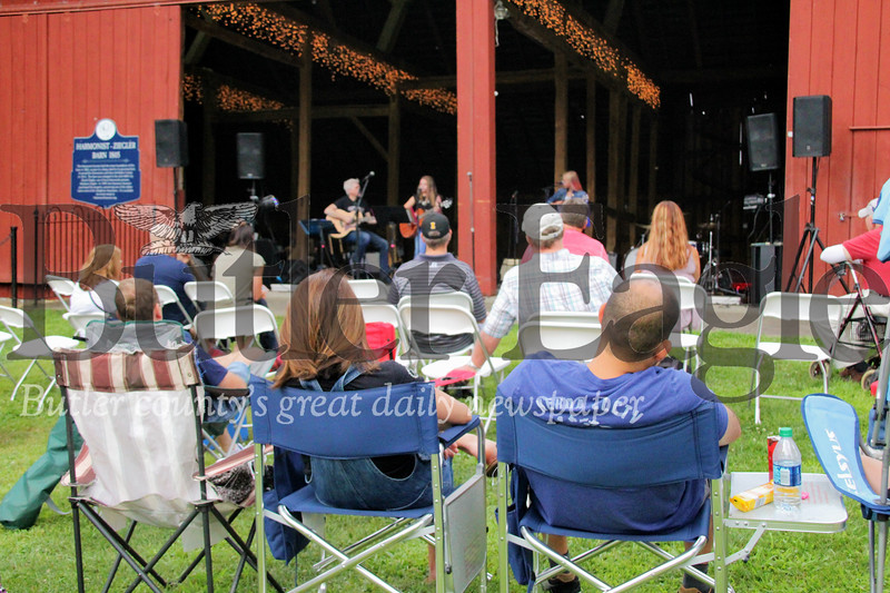 """Families watch Alexa Speicher, Ella Tirch and instructor Duane Davis on stage during the """"In Harmony"""" Heritage Music Festival, Saturday, at the Harmonist-Ziegler Barn."""