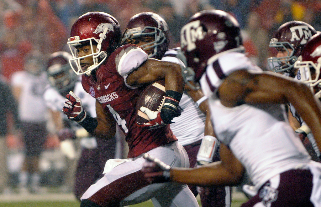 . Arkansas wide receiver Keon Hatcher (4) breaks through Texas A&M defenders on a punt-return during the third quarter of an NCAA college football game in Fayetteville, Ark., Saturday, Sept. 28, 2013. Texas A&M defeated Arkansas 45-33. (AP Photo/David Quinn)