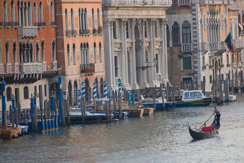 Gondolier steering an empty gondola over Grand Canal in Venice, Italy