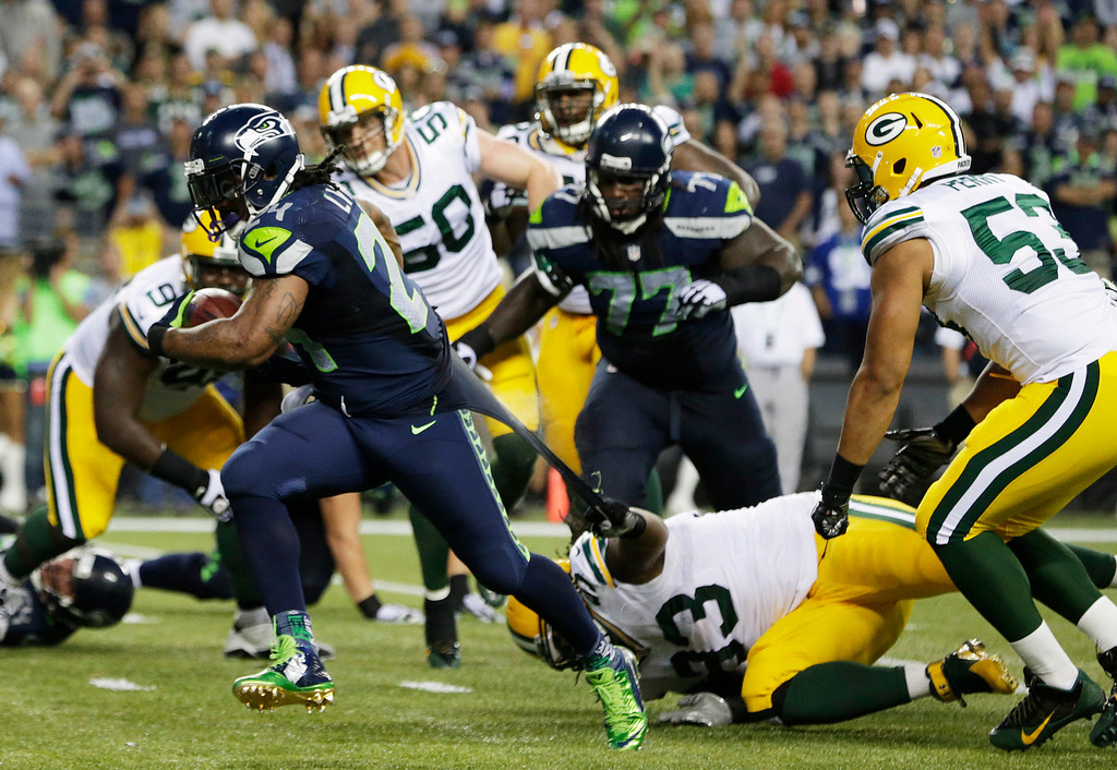 . Green Bay Packers defensive end Josh Boyd (93) grabs the jersey of Seattle Seahawks running back Marshawn Lynch, left, as Lynch runs for a touchdown in the second half of an NFL football game, Thursday, Sept. 4, 2014, in Seattle. (AP Photo/Scott Eklund)
