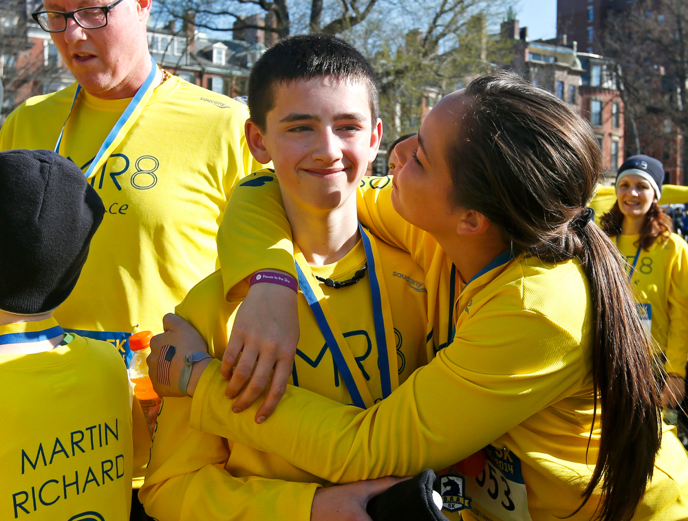 . Henry Richard, left, whose brother Martin was killed in the 2013 Boston Marathon bombings, is hugged after the Team MR8 group finished the Boston Marathon 5K in Boston, Saturday, April 19, 2014. The group was running for the Martin Richard foundation. (AP Photo/Elise Amendola)