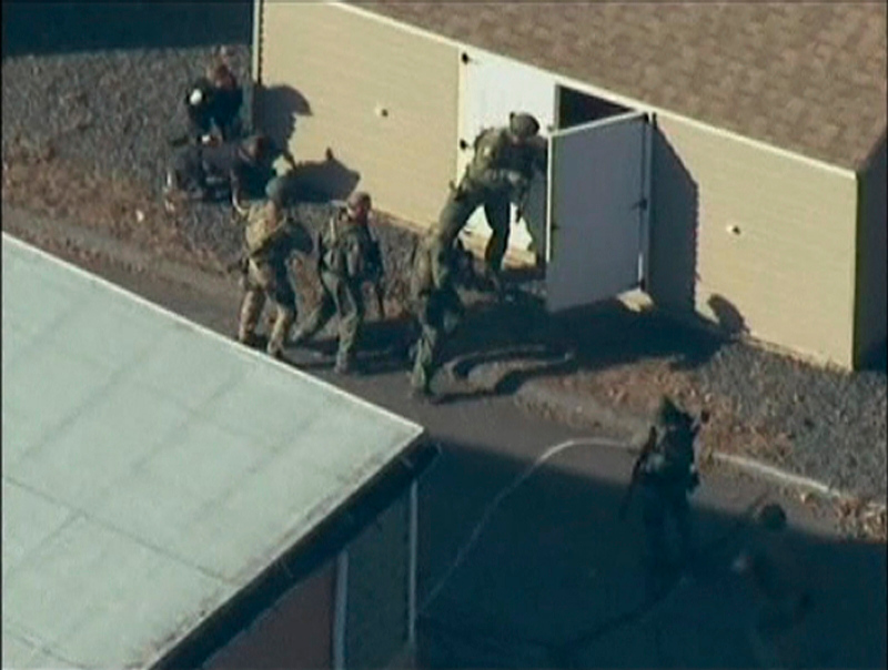 Description of . Police search a building after a shooting at Sandy Hook Elementary School in Newtown, Connecticut, December 14, 2012.  REUTERS/WNBC/Handout