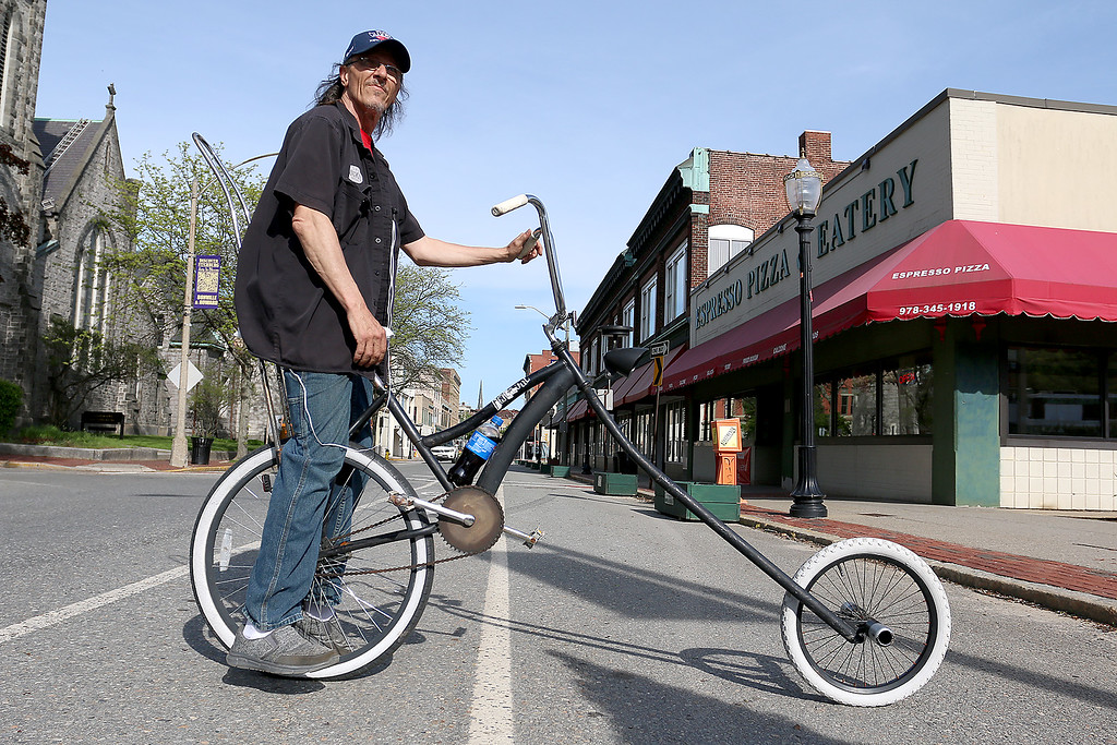 . Doug Easler, 49, of Fitchburg created his own bike out of parts from other bikes. He was caught riding it in the bike lane on Main Street in Fitchburg on Tuesday, May 16, 2017. A second bike is in the works and it will have two front tires and on rear. This bike has a solar powered front light. SENTINEL & ENTERPRISE/JOHN LOVE