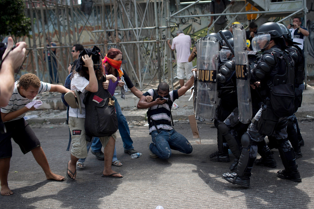 . Supporters of indigenous people occupying the old Indian Museum clash with riot police blocking the road outside the museum in Rio de Janeiro, Friday, March 22, 2013. The Indian museum has been at the center of a drawn-out legal battle between the several dozen Indians who\'ve been living there for years and state and local authorities. Officials initially wanted to raze the complex as part of renovations ahead of Brazil\'s 2014 World Cup. (AP Photo/Felipe Dana)