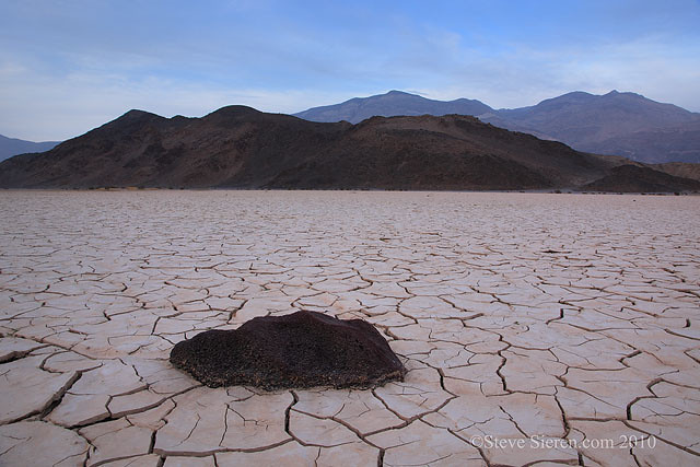 Volcanic rock and hill on dry lake bed in Death Valley