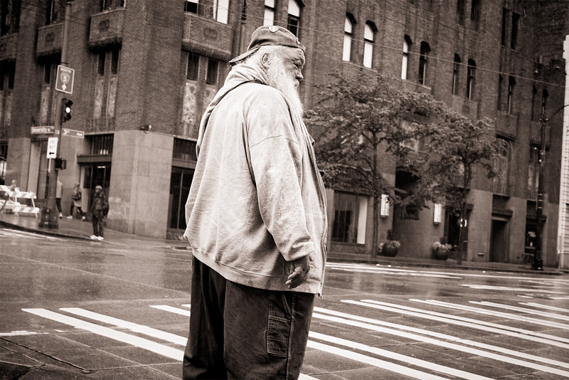 An older, bearded man waits to cross a Seattle street during a rainstorm.
