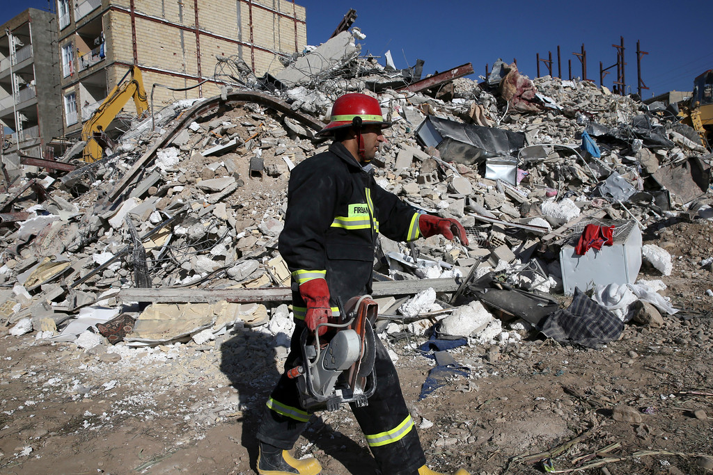 . A rescue worker walks past the rubble of a collapsed building at an earthquake site in Sarpol-e-Zahab in western Iran, Tuesday, Nov. 14, 2017. Rescuers are digging through the debris of buildings fallen by Sunday\'s earthquake in the border region of Iran and Iraq. (AP Photo/Vahid Salemi)