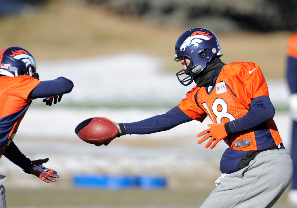 . Denver Broncos quarterback Peyton Manning (18) hands off to Denver Broncos running back Ronnie Hillman (21) during practice Wednesday, January 2, 2013 at Dove Valley.  John Leyba, The Denver Post
