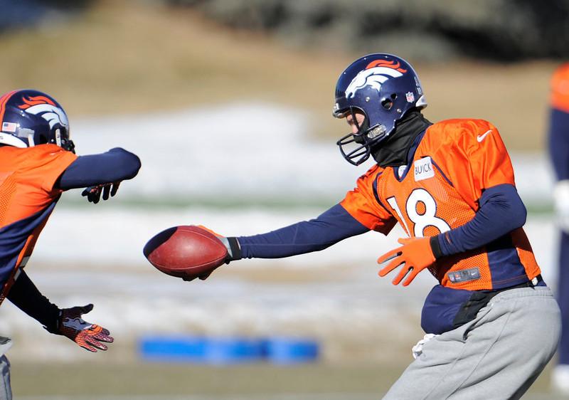 . Denver Broncos quarterback Peyton Manning (18) hands off to Denver Broncos running back Ronnie Hillman (21) during practice Wednesday, January 2, 2013 at Dove Valley.  John Leyba, The Denver Post
