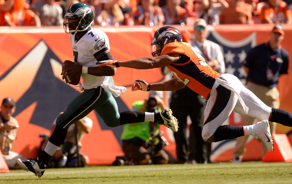 . Philadelphia Eagles quarterback Michael Vick (7) runs for the sidelines away from Denver Broncos outside linebacker Wesley Woodyard (52.) (Photo by John Leyba/The Denver Post)