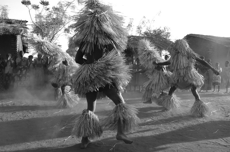 "Counselors from a Yao circumcision camp dance in the nearby village as a form of comfort and entertainment for the worried parents and realtives of the boys. Parents are not allowed to see their sons while the boys are sequestered in the exclusive camp during ""jando"", the Yao circumcision ceremony that marks the male passage into adulthood. Seeing the dancers from the encampment reassures everyone that everything is fine and the boys are doing well. Salima, Malawi. August 8, 2006"