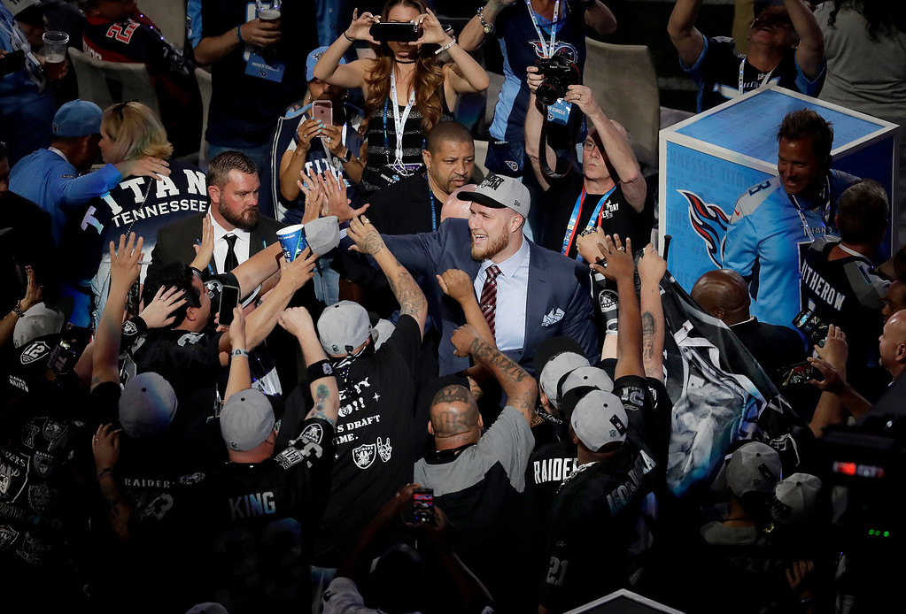 . UCLA\'s Kolton Miller, center, celebrates with Oakland Raiders fans after being selected by the team during the first round of the NFL football draft, Thursday, April 26, 2018, in Arlington, Texas. (AP Photo/Eric Gay)