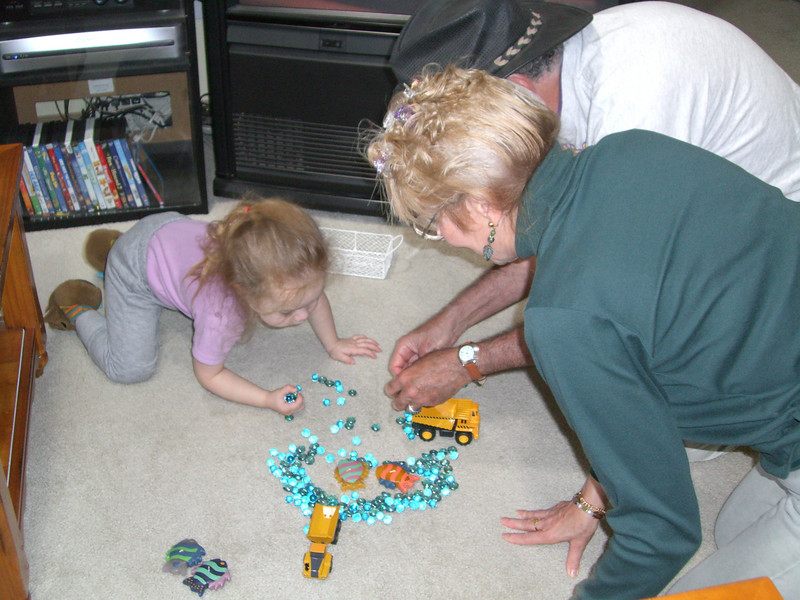Kimber, Grandmama and Papa Ben playing with trucks and marbles.