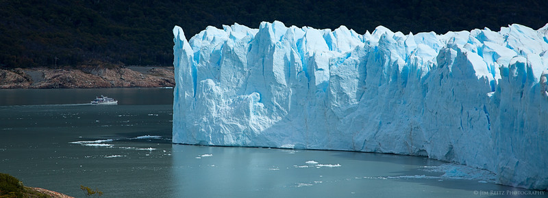 Perrito Moreno glacier in Patagonian Argentina. The passing tour boat provides a sense of the glacier's immense scale.