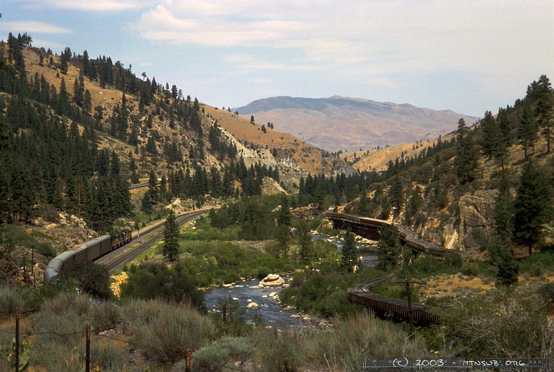 Near Mystic, the old wooden water funnel creates an odd contrast to the modern railroad and interstate. At the Nevada-California line, the scenery abruptly changes from dense forest to barren desert.