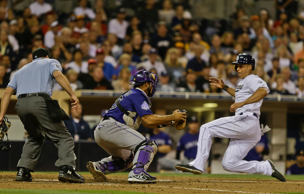 . San Diego Padres\' Will Venable slides into home where Colorado Rockies catcher Wilin Rosario waits to make the tag on a failed squeeze play in the seventh of a baseball game in San Diego, Tuesday, July 9, 2013. The umpire is Chris Guccione. (AP Photo/Lenny Ignelzi)