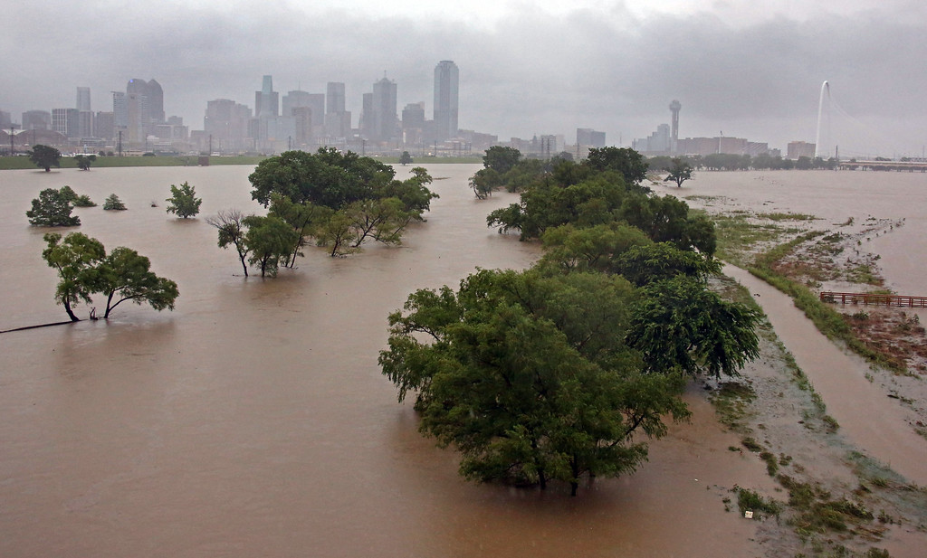 . With downtown Dallas in view, water from the Trinity River floods the area below the Sylvan Avenue bridge Monday, May 25, 2015, in Dallas. Several people were reported missing in flash flooding from a line of storms that stretched from the Gulf of Mexico to the Great Lakes. (Louis DeLuca/The Dallas Morning News via AP)
