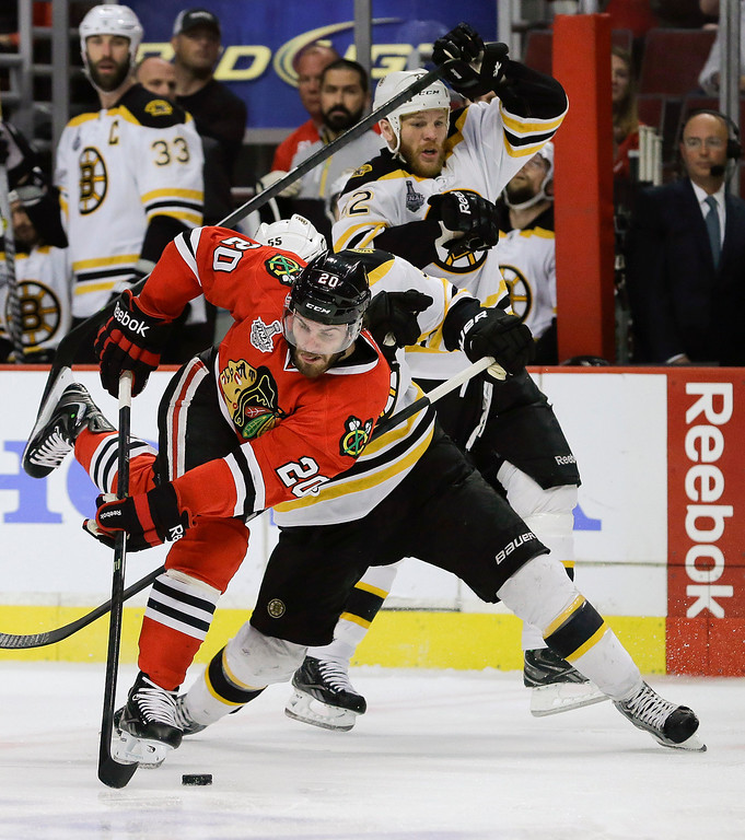 . Chicago Blackhawks left wing Brandon Saad (20) gets tangled up with Boston Bruins defenseman Johnny Boychuk (55) and Boston Bruins right wing Shawn Thornton (22) in the second period during Game 5 of the NHL hockey Stanley Cup Finals, Saturday, June 22, 2013, in Chicago. (AP Photo/Nam Y. Huh)
