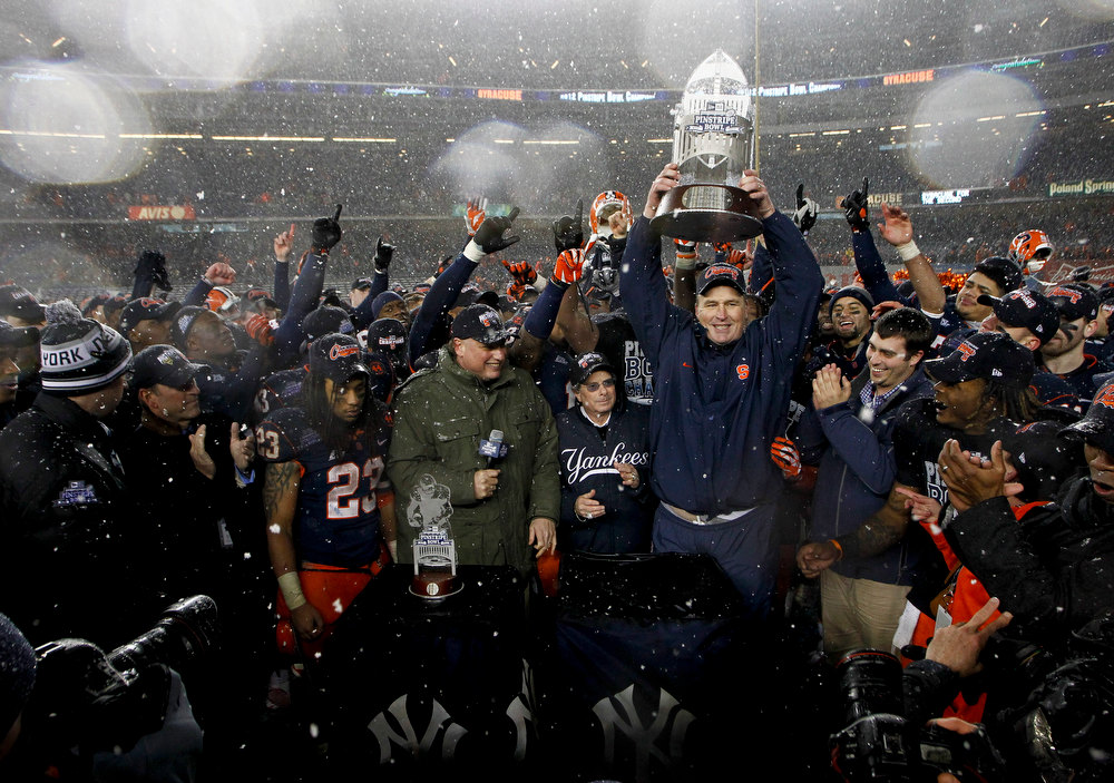 Description of . Head coach Doug Marrone of the Syracuse Orange hoists the trophy after victory over the West Virginia Mountaineers in the New Era Pinstripe Bowl at Yankee Stadium on December 29, 2012 in the Bronx borough of New York City.  (Photo by Jeff Zelevansky/Getty Images)