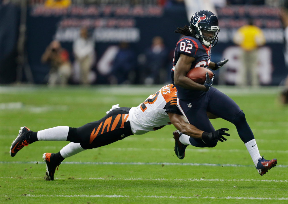Description of . Houston Texans wide receiver Keshawn Martin (82) is tackled by Cincinnati Bengals strong safety Nate Clements (22) during the first quarter of an NFL wild card playoff football game Saturday, Jan. 5, 2013, in Houston. (AP Photo/Eric Gay)