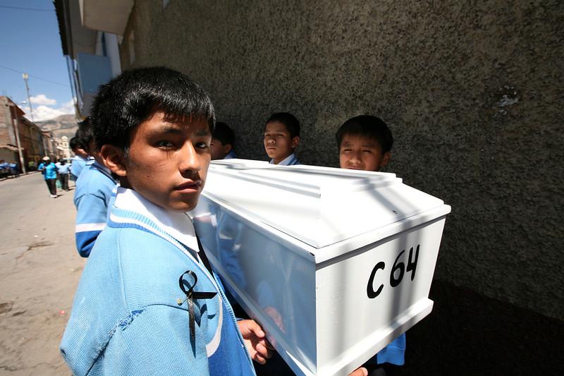 Los escolares de los colegios locales ayudaron en el transporte de los féretros. / Local school students assisted in moving the coffins. foto: Marina García Burgos