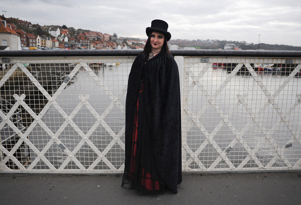 . WHITBY, ENGLAND - NOVEMBER 02: Jean Clarkson, a hotel worker from Bishop Aukland stands on the main bridge as she takes part in the Goth weekend on November 2, 2013 in Whitby, England. The Whitby Gothic Weekend that takes place in the Yorkshire seaside town twice yearly in Spring and Autumn started in 1994 and sees thousands of extravagantly dressed followers of Victoriana, Steampunk, Cybergoth and Romanticism visit to take part in celebrating Gothic culture.  (Photo by Ian Forsyth/Getty Images)