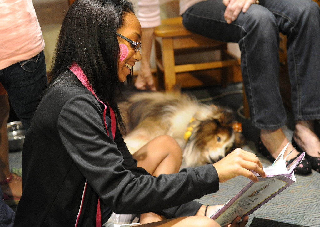 . (John Valenzuela/Staff Photographer) Aziah James 12, of Highland, reads to Robbie the Dog during the 10th Annual Family Day at the A.K. Smiley Library in Redlands, Saturday Oct. 5, 2013.