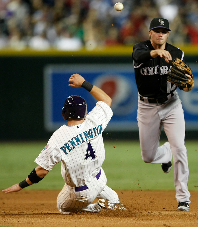 . Colorado Rockies shortstop Josh Rutledge, right, turns a double play while avoiding Arizona Diamondbacks\' Cliff Pennington (4) in the sixth inning during a baseball game, Saturday, Aug. 30, 2014, in Phoenix. (AP Photo/Rick Scuteri)
