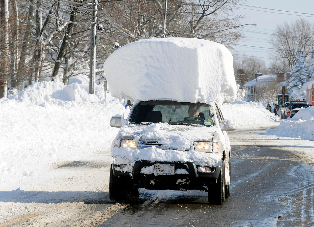 . A vehicle, with a large chunk of snow on its top, drives along Route 20 after digging out after a massive snow fall in Lancaster, N.Y. Wednesday, Nov. 19, 2014. Another two to three feet of snow is expected in the area. (AP Photo/Gary Wiepert)