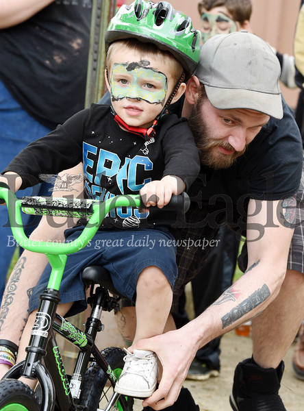 Harold Aughton/Butler Eagle: Chris Nunez of Butler gives his son, Lucca, 3, a quick lesson on how to ride a bike at the Butler Bike Rodeo held Sunday afternoon, May 5.