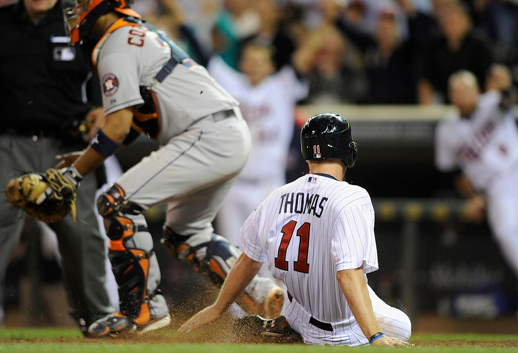 . Clete Thomas #11 of the Minnesota Twins slides safely into home with the winning run as Carlos Corporan #22 of the Houston Astros waits for the throw. (Photo by Hannah Foslien/Getty Images)