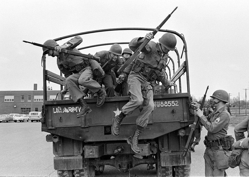 . Tennessee National Guard troops leap out of a truck at the Memphis Armory after being ordered into the city by Gov. Buford Ellington at the request of city officials, March 28, 1968. The guard was ordered after rioting and looting erupted midway through a march led by Dr. Martin Luther King Jr., in support of striking garbage workers. (AP Photo/Jack Thornell)