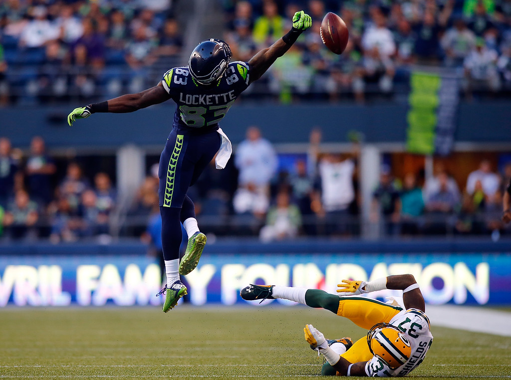 . SEATTLE - SEPTEMBER 04: Wide receiver Ricardo Lockette #83 of the Seattle Seahawks goes up in attempt to catch a pass as cornerback Sam Shields #37  of the Green Bay Packers falls to the turf  during the third quarter of the game at Century Link Field on September 4, 2014 in Seattle, Washington.  (Photo by Jonathan Ferrey/Getty Images)