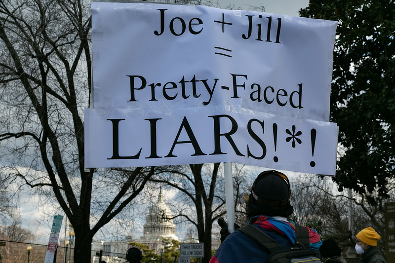A lone protestor holds a sign in a crowd of onlookers near the U.S. Capitol as the inauguration ceremonies begin