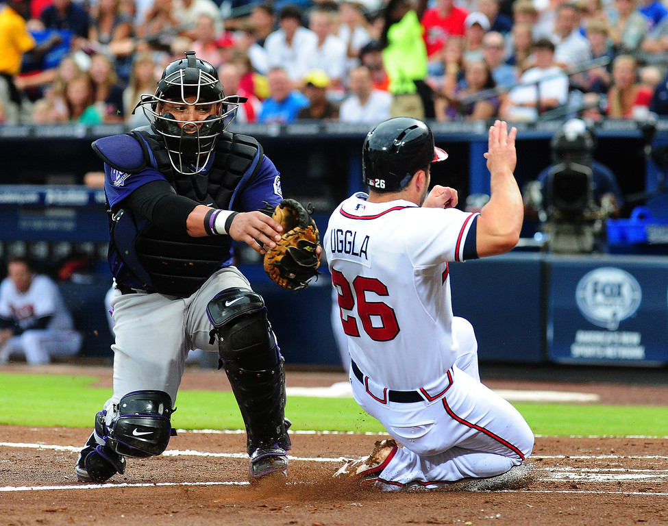 . Dan Uggla #26 of the Atlanta Braves is tagged out at home by Yorvit Torrealba #8 of the Colorado Rockies at Turner Field on July 31, 2013 in Atlanta, Georgia. (Photo by Scott Cunningham/Getty Images)