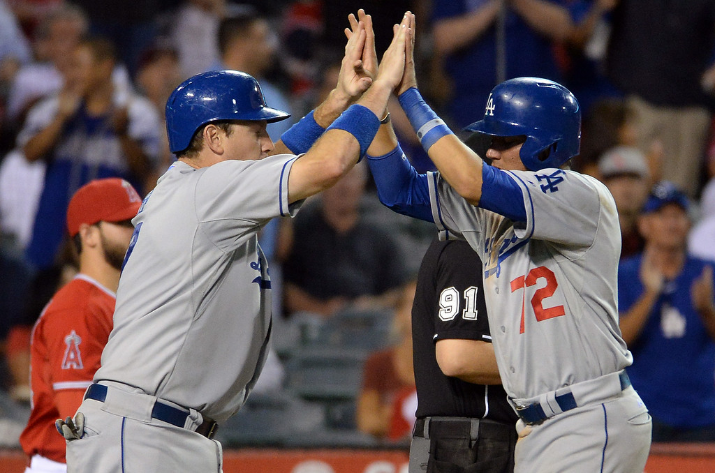 . Los Angeles Dodgers\' A.J. Ellis high fives teammate Miguel Rojas (72) after scoring on a RBI single by Adrian Gonzalez (not pictured) in the eighth inning of a baseball game against the Los Angeles Angels at Anaheim Stadium in Anaheim, Calif., on Thursday, Aug. 7, 2014.  (Photo by Keith Birmingham/ Pasadena Star-News)