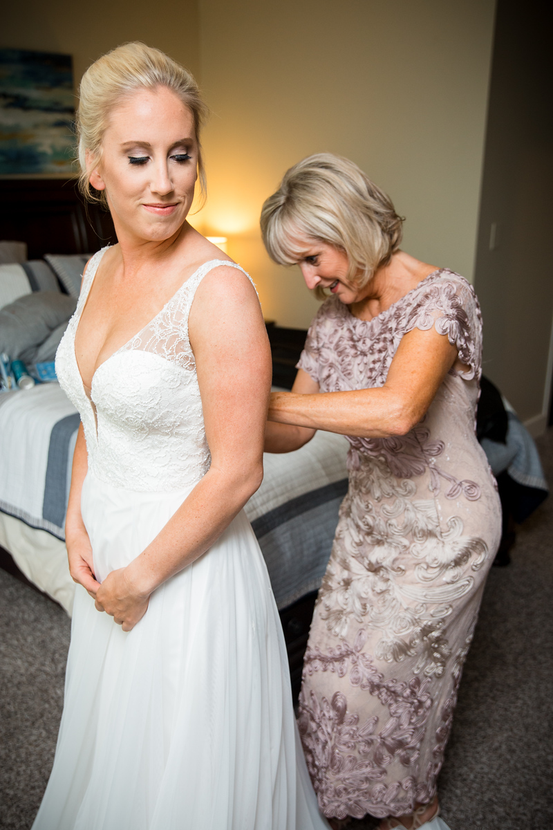 a woman buttoning her daughter's wedding dress before her wedding