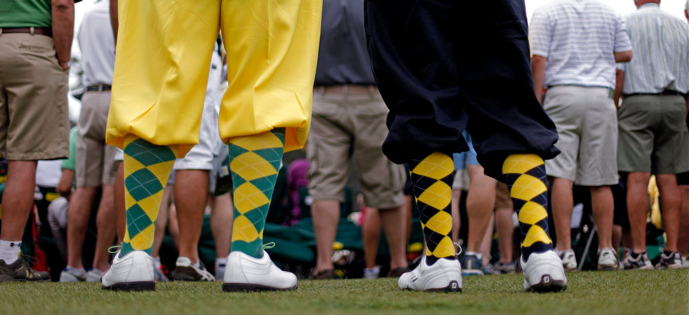 Description of . Richard Walker, left, and his son Billy, from Yorkshire, England, wear golf knickers as they watch the fourth round of the Masters golf tournament Sunday, April 14, 2013, in Augusta, Ga. (AP Photo/David Goldman)