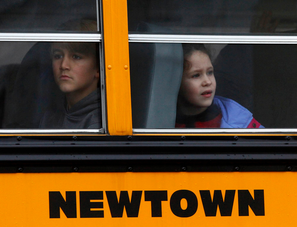 Description of . Students ride a school bus in Newtown, Connecticut December 18, 2012. The schools of Newtown, which stood empty in the wake of a shooting rampage that took 26 of their own, will again ring with the sounds of students and teachers on Tuesday as the bucolic Connecticut town struggles to return to normal. REUTERS/Eric Thayer
