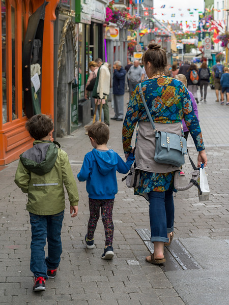 Mother walking down the market street with her children, Galway City, County Galway, Ireland