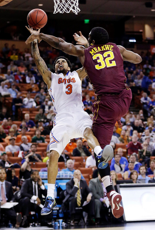 . Florida\'s Mike Rosario (3) is fouled by Minnesota\'s Trevor Mbakwe (32) during the first half of a third-round game of the NCAA college basketball tournament, Sunday, March 24, 2013, in Austin, Texas. (AP Photo/Eric Gay)