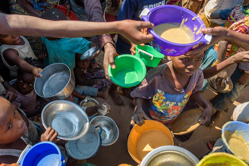 Children hold up their bowls, eager for porridge handed out during supplemental feeding at the Child Friendly Space that Marie Ngalula, 14, and her siblings attend.  Marie lives with her father, Alexandre Tshimanga, her mother, Ntumba Kalombo Antoinette and her brothers and sisters: 1-Kena Tshimanga, 12 2-Kankonde Moise, 10 3-Munamba Angel, 8 4-Musungayi Andre, 6 5-Mubuyi Tshimanga, 4  Marie lives in a small village outside of Kananga, Democratic Republic of Congo, DRC, called Tubuluku, which means antelopes (plural). Her house is a two-room hut with a thatched roof.  Handful of wooden chairs are the only furniture. She lives here with an extended family of 13.  Home Life Marie is a bright girl but there is a sadness in her eyes. Marie's mother is in the nearby health clinic with a staph infection that has caused a huge abscess on her right side. It has become very serious. As a result, Marie has assumed many of the household duties.  She's forced, at 14, to assume the duties of an adult. Besides cooking for her brothers and sisters, she sweeps up the husks from palm nuts she crushes. She saves the husks to use as kindling for the fire. Marie and her siblings all sleep together in one room, huddled together for warmth and cover by an old and torn mosquito net.  Hunger Marie's family is desperately hungry in the days we visit them. Because her mother is sick and his father spends his days tending to her in the clinic, there is no money for food. Because there isn't any cassava flour and cornmeal to make fufu, a bread-like dish that's a Congolese staple, Marie and her siblings pick potato leaves from the garden. Marie sharpens a knife on a rock and uses it to chop the leaves into small pieces. She holds a bunch tightly in her left hand and runs the knife through them.  Her cousin, also named Marie Ngalula, pulls some wood from a pile and arranges it between three rocks that will hold the pot. She yanks some thatch from the roof and uses it for kindling. Because they a