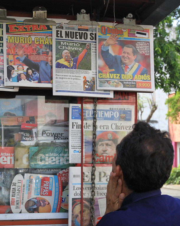 . A man reads the news of Venezuela\'s late President Hugo Chavez on the newspapers in a newspaper stand in Cali March 6, 2013. REUTERS/Jaime Saldarriaga