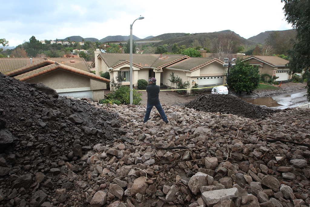 . Local resident Erwin Fodran surveys damage from atop a pile of rocks and mud after debris flows smashed into houses as a powerful storm that has been lashing northern California moves southward on December 12, 2014 in Camarillo Springs neighborhood of Camarilla, California.   (Photo by David McNew/Getty Images)