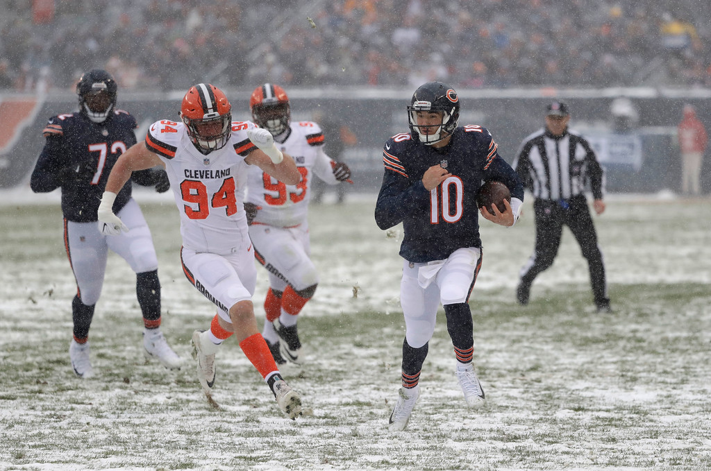 . Chicago Bears quarterback Mitchell Trubisky (10) runs as Cleveland Browns defensive end Carl Nassib (94) chases in the first half of an NFL football game in Chicago, Sunday, Dec. 24, 2017. (AP Photo/Charles Rex Arbogast)