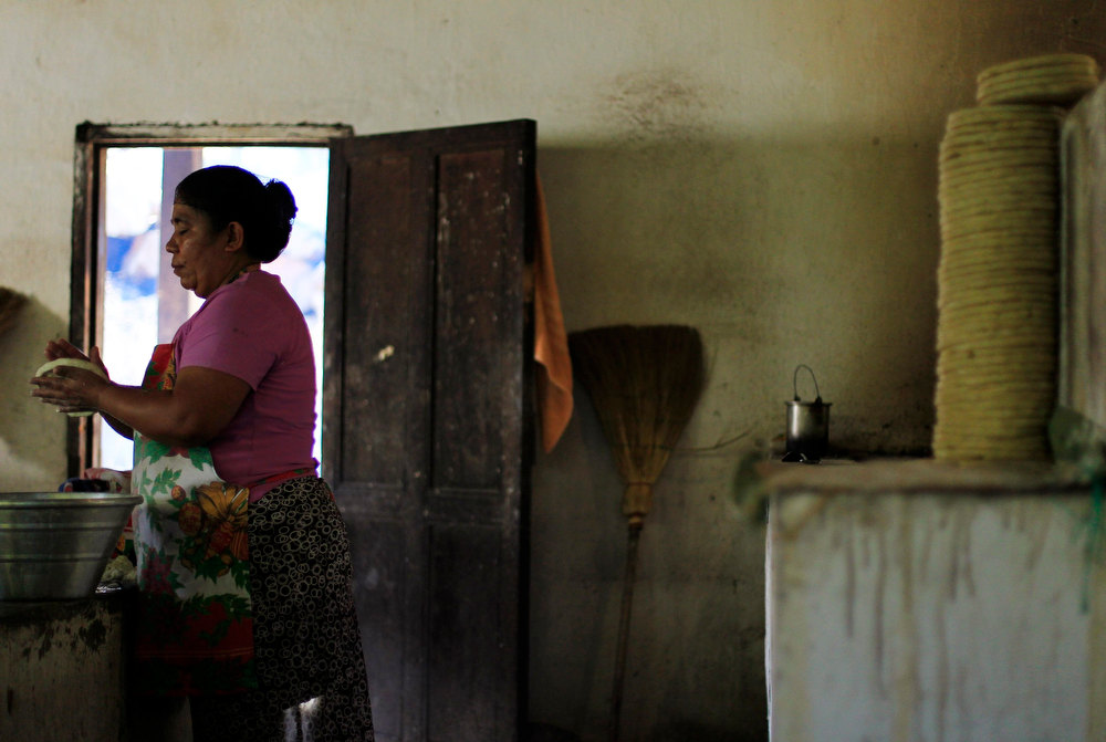 . A woman prepares tortillas for lunch at the Santa Adelaida coffee cooperative in La Libertad, on the outskirts of San Salvador December 10, 2012. Once a family-owned coffee plantation split under a 1980 land reform, the Santa Adelaida coffee is now a cooperative dedicated to the production of organically-grown high ground coffee, which is certified by non-governmental organization Rainforest Alliance, and exported to Germany, the U.S., Britain and Japan. The coffee plantation is currently run by a cooperative of over 150 members. Picture taken December 10, 2012. REUTERS/Ulises Rodriguez