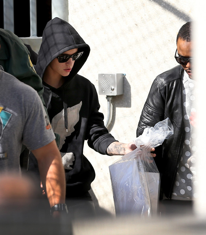 . Justin Bieber (L) exits from the Turner Guilford Knight Correctional Center on January 23, 2014 in Miami, Florida. Justin Bieber was charged with drunken driving, resisting arrest and driving without a valid license after Miami Beach police found the pop star street racing Thursday morning.  (Photo by Joe Raedle/Getty Images)